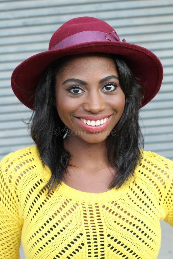 Flippige Artschönheit Porträt der schönen jungen Afrikanerin im flippigen Hut lächelnd bei der Stellung gegen grauen städtischen  stockbild
