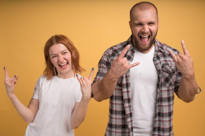 Flippige verrückte Gefährten zeigen Geste des Rocks n Rollen, Schrei von der Freude, sich freuen die Anhörungsmusik der Lieblings stockfotografie