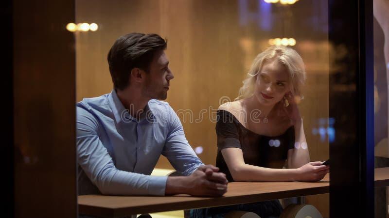 Flirt abbastanza femminile con il giovane al caff?, uguagliante ora, raccolta e data fotografia stock
