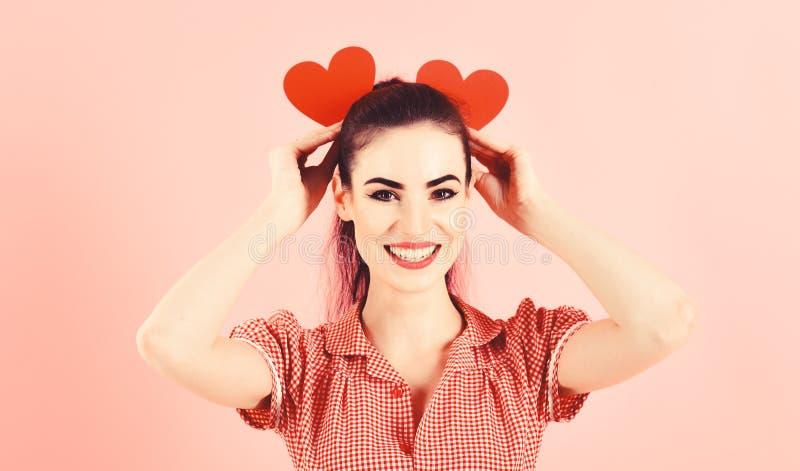 Flirt, emozioni, biglietto di S. Valentino, buon concetto di umore La ragazza con il fronte allegro, compone e cuori rossi giovan immagine stock libera da diritti