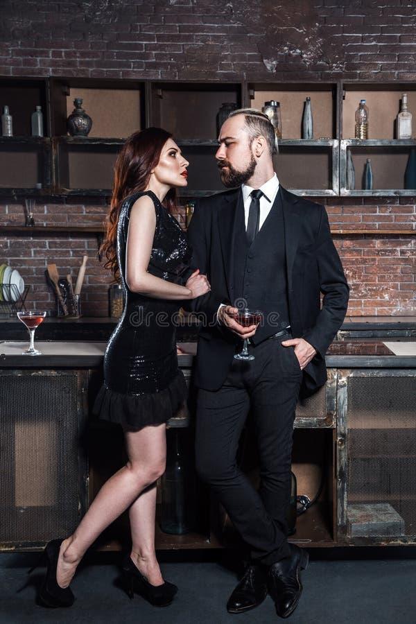 Flirt op een partij De glazen van de meisjesholding van wijnstok en het kijken met hartstocht op de gebaarde mens stock foto's