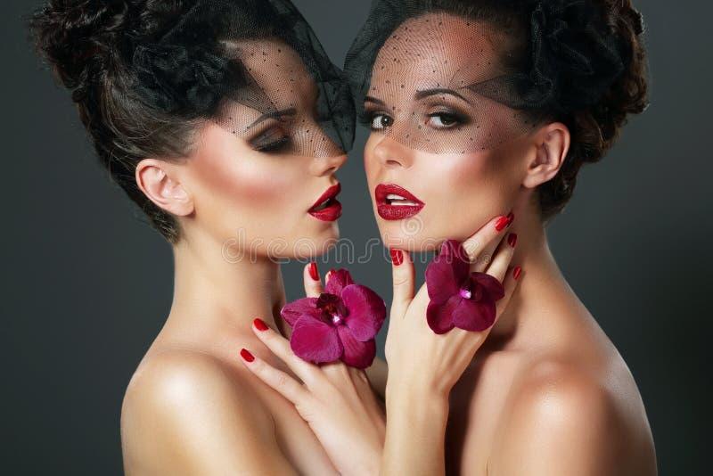 Flirt. Portrait of Two Voluptuous Romantic Women with Violet Orchids stock photos