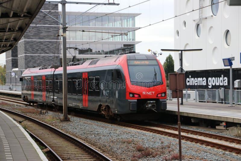 Flirt train in black and red R-NET color along platform at station Gouda heading Alphen aan den Rijn stock image