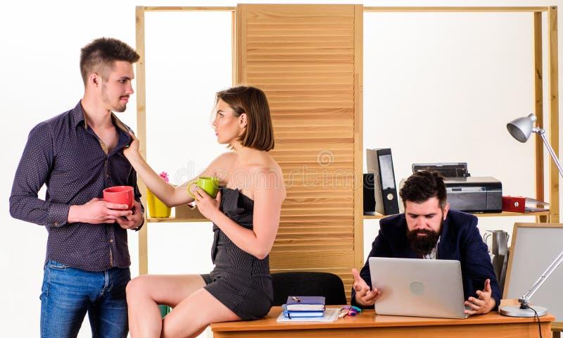 Flirtando durante i responsabili di resto che bevono tè nell'ora di resto Giovani colleghe che godono della pausa sul lavoro Donn fotografia stock libera da diritti