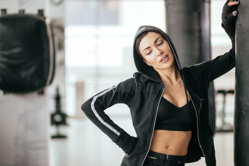 Flirtatious woman in black sweatshirt leaning on huge punching bag stock images