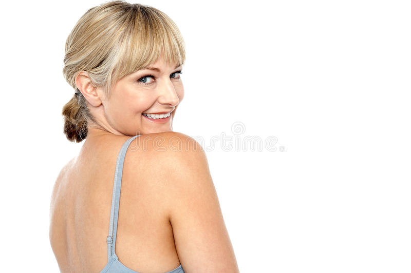 Flirtatious woman turning back and passing a smile stock images
