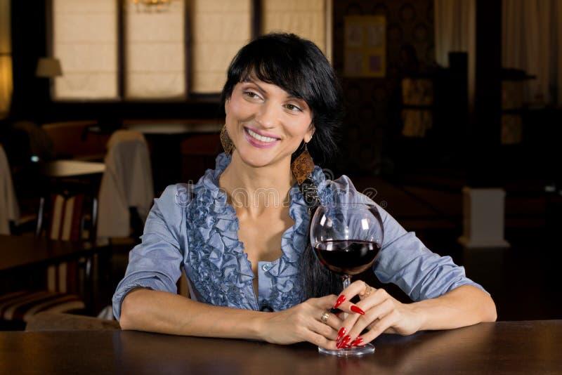 Flirtatious young woman drinking at a bar stock photos