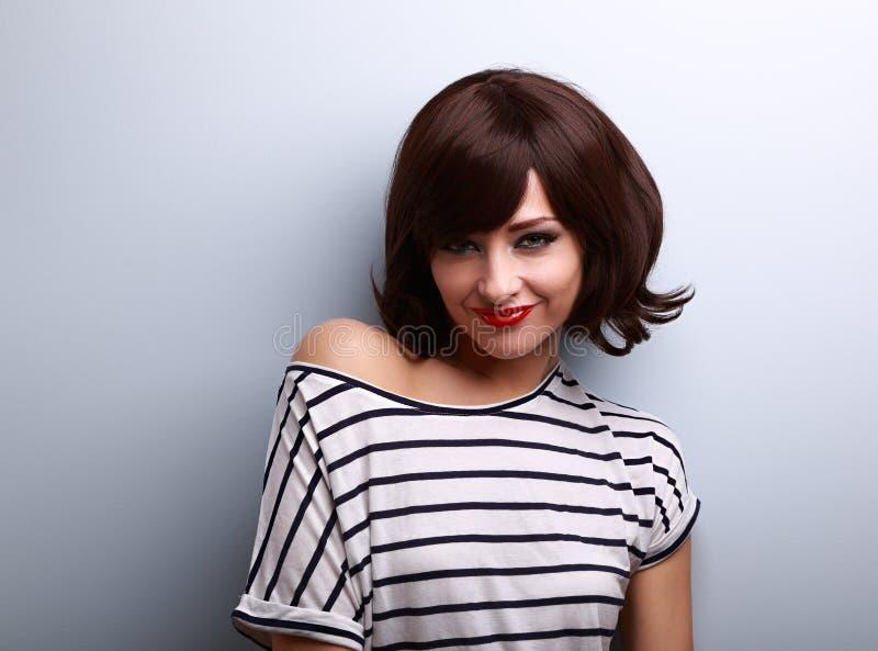 Flirtende junge Frau mit kurzer Frisur und roter Lippenstift schauen stockfotografie