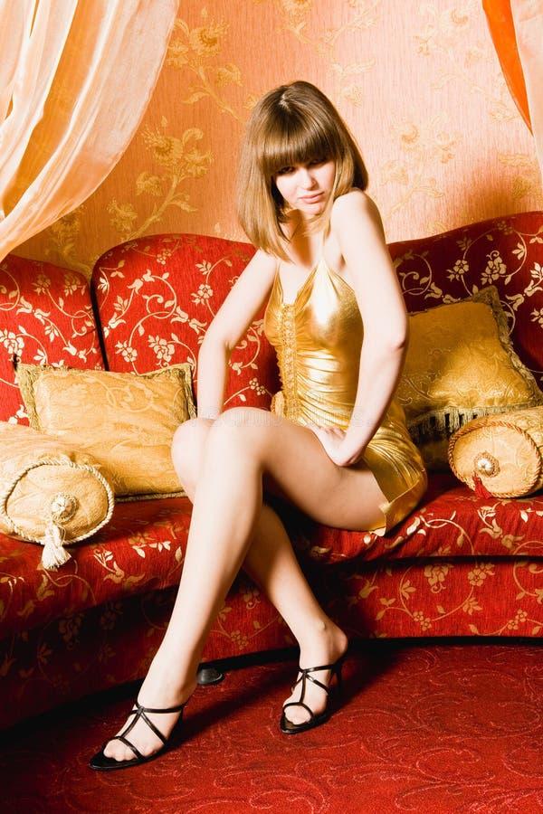 Flirtende vrouw in gouden kleding royalty-vrije stock afbeelding