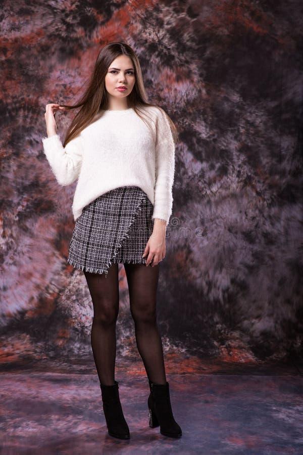 Flirtigt härligt plus formatkvinna i en ljus färgad tröja och en kjol på en marmor färgade bakgrund arkivbilder
