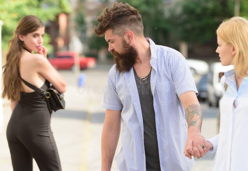 Flirting в улице Любовный треугольник и threesome Человек обжуливая его подругу Бородатый человек смотря другую девушку стоковая фотография rf