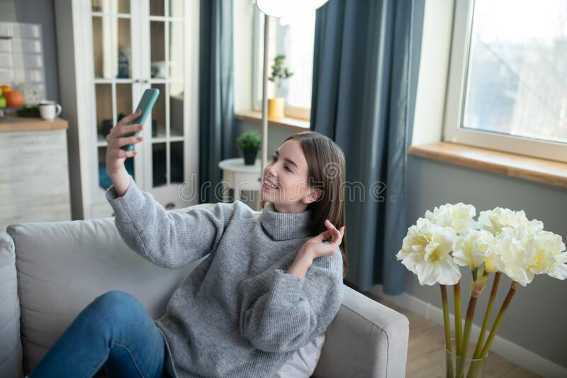 Dark-haired girl in a grey sweater looking flirty stock photography