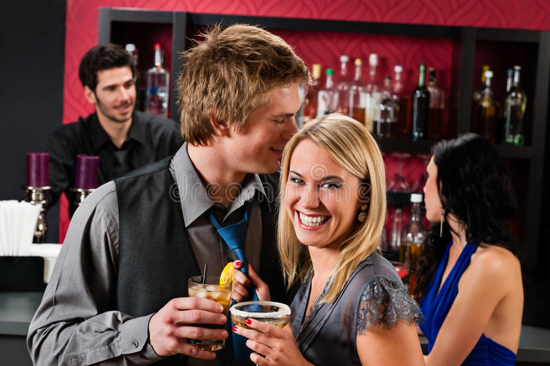 Flirting happy friends drinks at cocktail bar royalty free stock photo