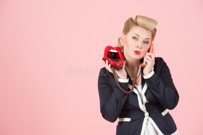 A Flirting portrait of blonde girl with phone in pin-up make-up with copyspace area for advertising text message royalty free stock photo
