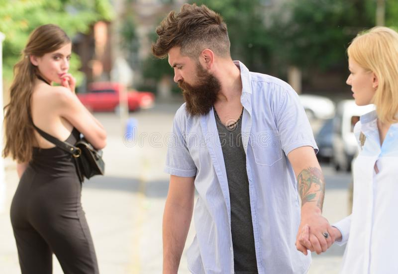 Flirting in the street. Love triangle and threesome. Man cheating his girlfriend. Bearded man looking at other girl. Flirting in the street. Love triangle and royalty free stock photography