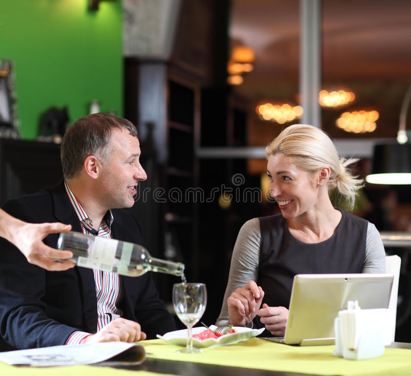 Flirtować pary w kawiarni używać cyfrową pastylkę obraz royalty free