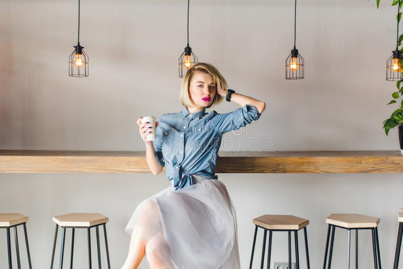 Flirty blond girl with blue eyes and bright pink lips sitting in a coffee shop on a chair drinking coffee and playing royalty free stock images
