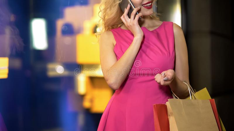 Flirty blonde having phone conversation, luxury shopping at fashion boutique stock photo
