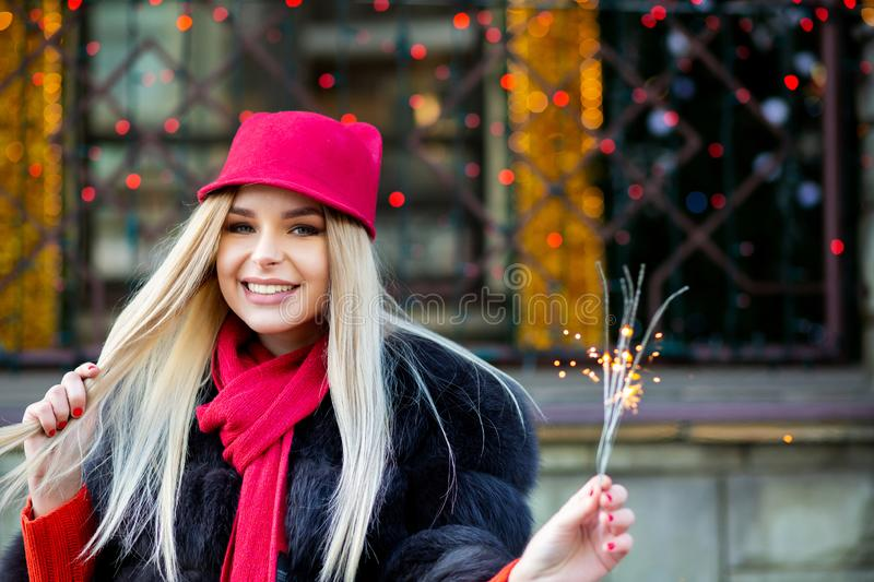 Flirty blonde model celebrating New Year with sparklers at the b stock image