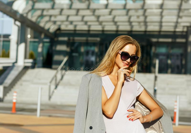 Flirty blonde woman in stylish glasses posing at the avenue in s royalty free stock image