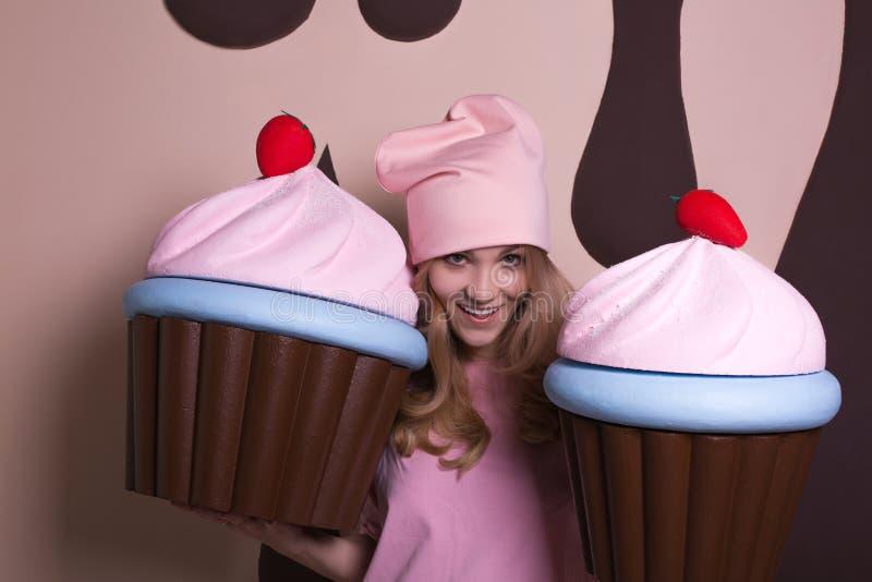 Flirty blonde woman wearing pink cap enjoying big cupcakes at studio royalty free stock images