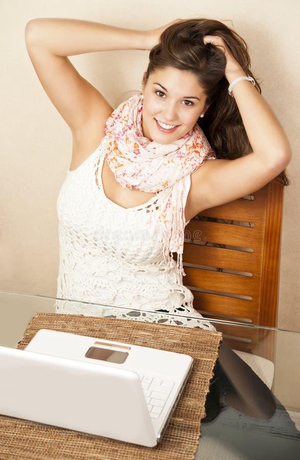 Flirty flicka framme av henne bärbar dator royaltyfri fotografi
