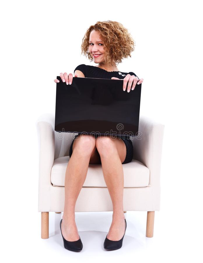 Flirty girl with laptop. Flirty young beautiful woman sitting in armchair with laptop - isolated stock photography