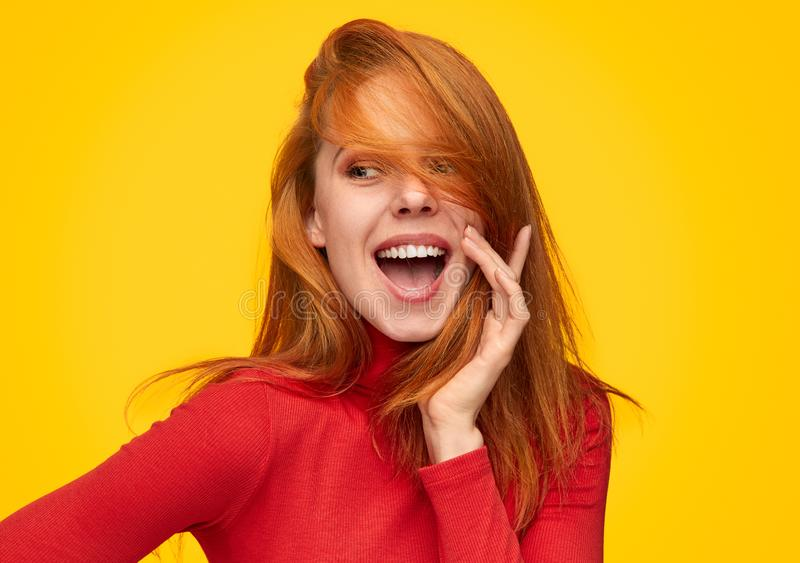 Charming ginger girl in red turtleneck. Flirty happy redhead girl posing with bright smile on orange background royalty free stock photo