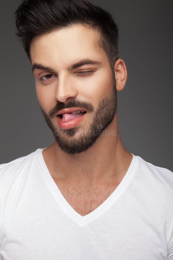 Flirty junger Mann, der heraus seine Zunge und Winks haftet lizenzfreies stockfoto