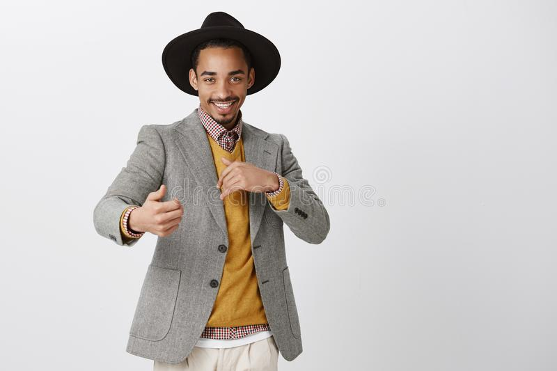 Flirty romantic male wanting have fun. Studio shot of satisfied confident african-american man in stylish black hat and stock image