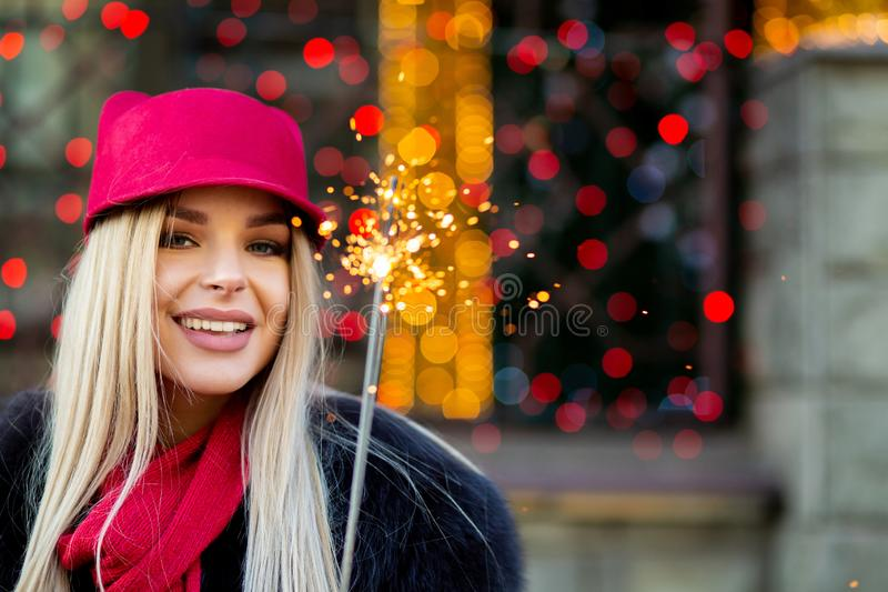 Flirty smiling blonde model wearing fashionable winter outfit, h stock photography