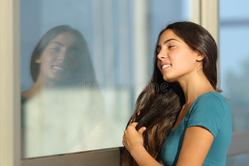 Flirty teen girl combing her hair using a window like a mirror. Outdoor in the street stock photography