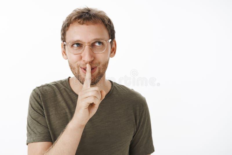 Flirty und frecher Kerl, der faszinierendes geheimes hat, es mit dem engen Freund teilend, der flirty und unterhaltenes Betrachte stockfoto