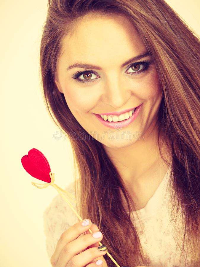 Flirty woman holding red wooden heart on stick stock photo