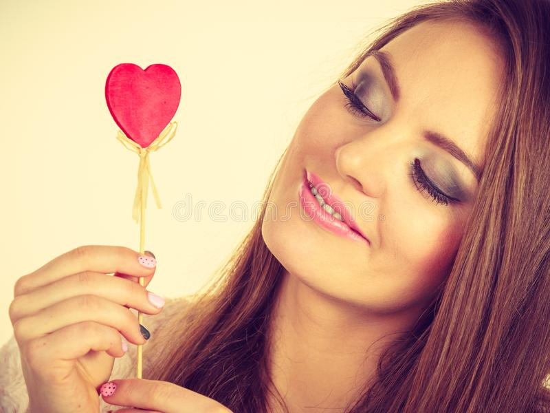 Flirty woman holding red wooden heart on stick royalty free stock images