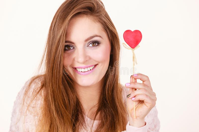Flirty woman holding red wooden heart on stick royalty free stock image
