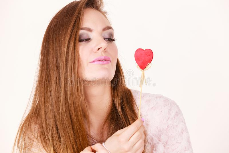 Flirty woman holding red wooden heart on stick royalty free stock photos