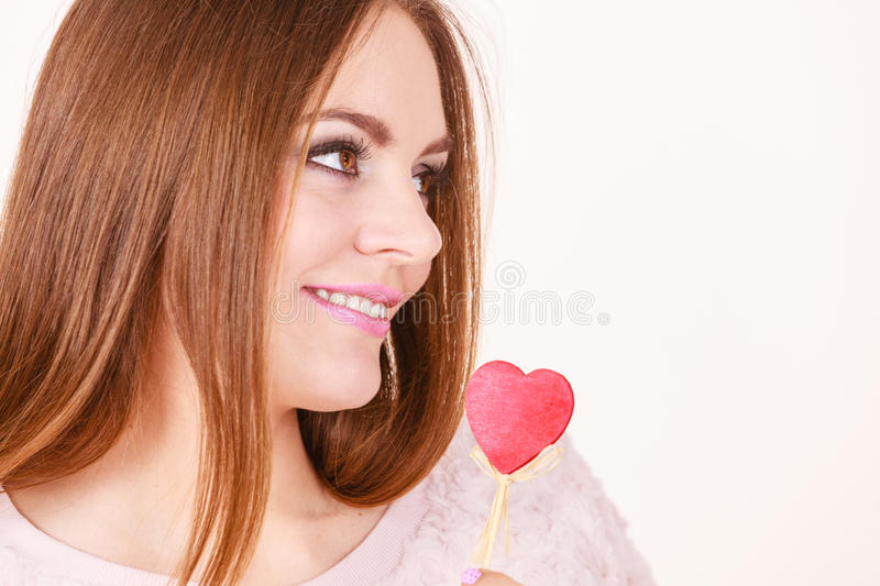 Flirty woman holding red wooden heart on stick stock images