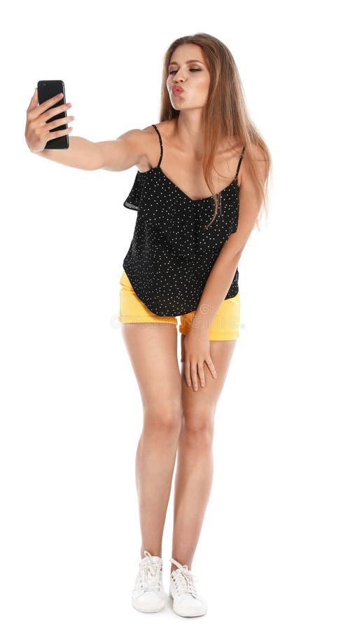 Flirty young woman taking selfie on white royalty free stock photos