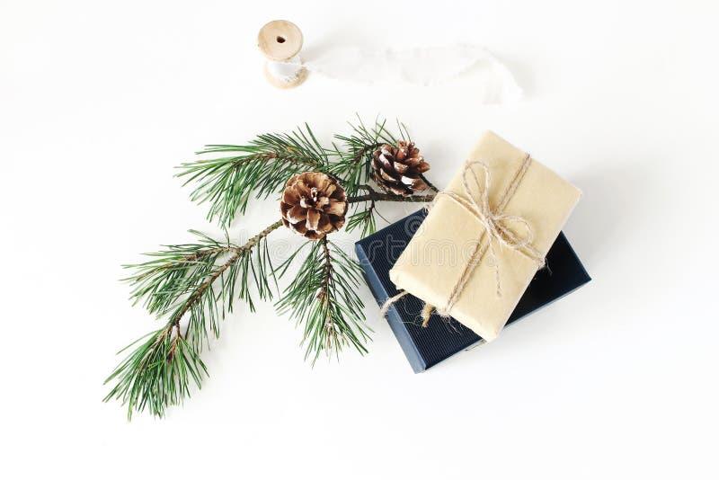 Flitter in einem blauen Glas Festliche eingewickelte Weihnachtsgeschenkboxen mit Kiefernniederlassung mit Kegeln und Seidenband a stockfoto