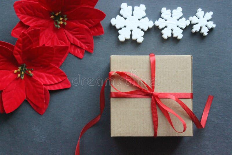 Flitter in einem blauen Glas Geschenkbox mit rotem Satinband, -holz und -schneeflocken auf schwarzem Hintergrund Spielwaren-Weihn lizenzfreie stockbilder