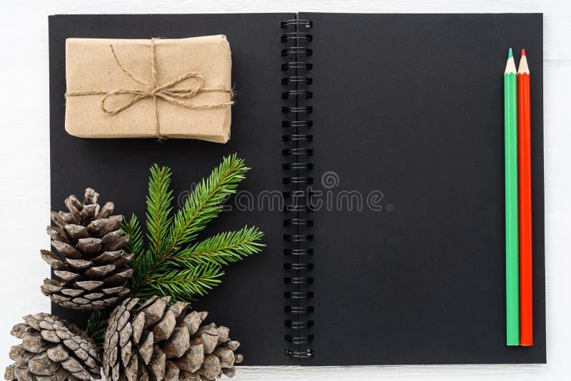 Flitter in einem blauen Glas Schwarzes Notizbuch mit Dekorationen des neuen Jahres stockbild