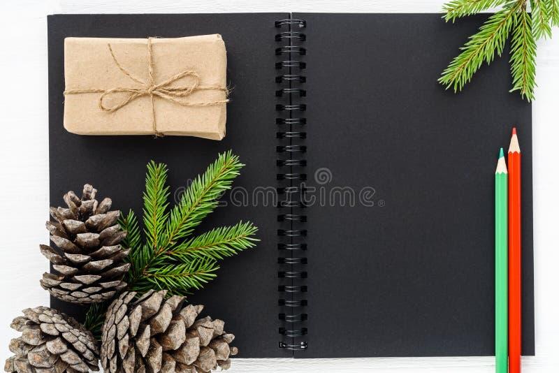 Flitter in einem blauen Glas Schwarzes Notizbuch mit Dekorationen des neuen Jahres stockfotos