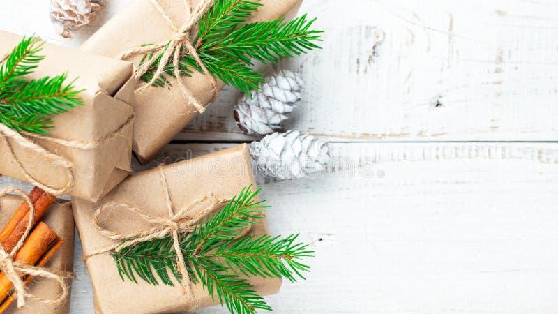 Flitter in einem blauen Glas Weihnachtsgeschenk, Kiefernkegel, Tannenzweige auf hölzernem weißem Hintergrund Flache Lage, Draufsi stockfotografie