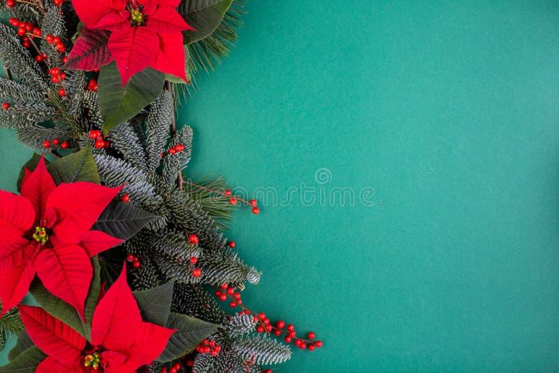 Flitter in einem blauen Glas Weihnachtsgründekorationen, Tannenbaumaste mit roten Blumen auf grünem Hintergrund Flache Lage stockfotos