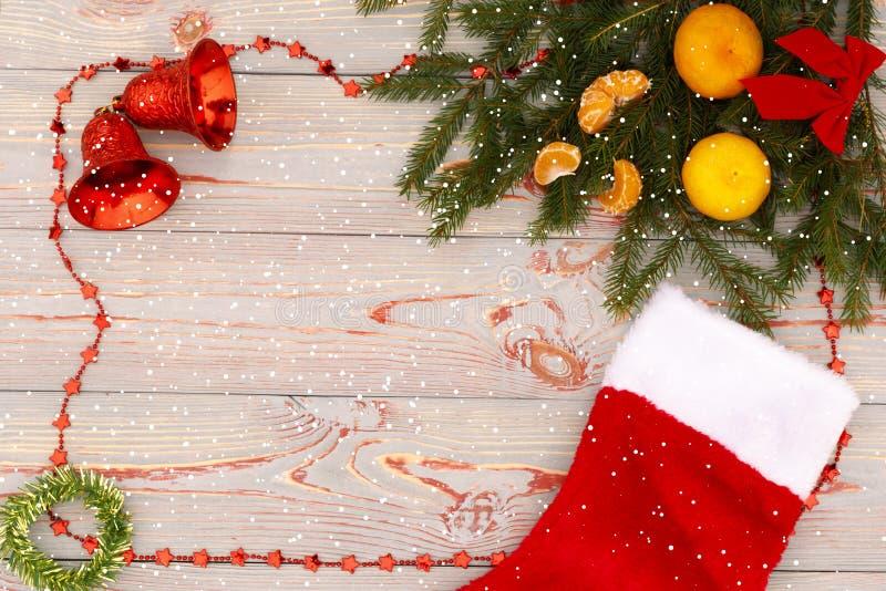 Flitter in einem blauen Glas Weihnachtsmuster mit Tangerinen, Tannenzweig, rote Socke für ein Geschenk und Draufsicht der Glocken stockfotografie