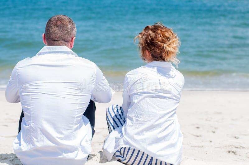 flitterwochen Glückliches Paar, das auf tropischem Strand sitzt stockbild