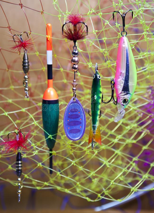Float and baits on a fishing net background.  royalty free stock photo