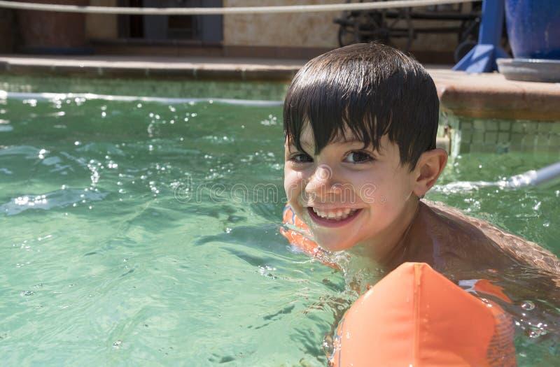 Floaties del brazo del muchacho que llevan en una piscina fotos de archivo libres de regalías
