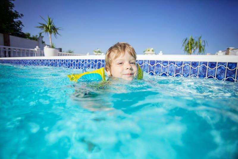 Floaties vestindo do menino louro feliz e nadar fora foto de stock